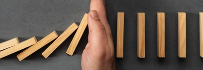 Hand stopping dominoes from cascading